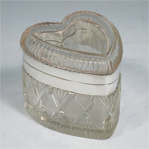 A very pretty and unusual Antique Sterling Silver and hand-cut crystal jewellery box, having a heart-shaped hand-cut crystal body, with plain silver mounted borders, and a twin-hinged lid, all sitting on a flat base. Made by Thomas Wheeler of London in 1896. The dimensions of this fine hand-made silver and crystal jewelery box are length 9 cms (3.5 inches), width 8 cms (3 inches), and height 8 cms (3 inches).