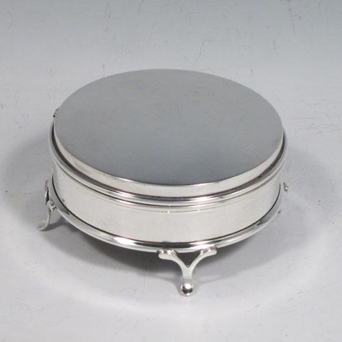 Sterling silver jewellery box, having a plain round body, with hinged lid and a gold-gilt interior, blue-velvet lined base, all sitting on four pierced feet. Made by Charles Edwards of London in 1920. The dimensions of this fine hand-made silver jewelery box are diameter 9 cms (3.5 inches), and height 5 cms (2 inches).