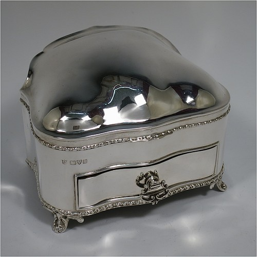 An Antique Edwardian Sterling Silver large jewellery box, having a rectangular shaped casket style body with rounded corners and applied pearl and bead borders, a plain domed hinged lid covering a velvet-lined interior, a pull-out drawer with a cast swing handle, and all sitting on four cast foliate feet. Made by Nathan and Hayes of Chester in 1907. The dimensions of this fine hand-made antique silver jewellery box are length 13.5 cms (5.3 inches), width 11 cms (4.3 inches), and height 11 cms (4.3 inches).