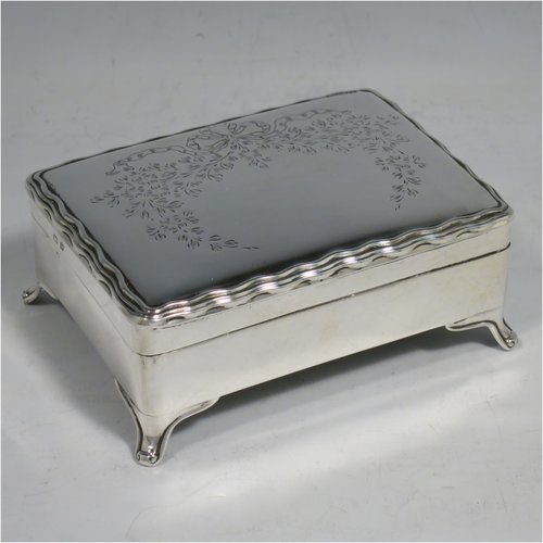 A Sterling Silver very pretty jewellery box, having a rectangular shaped body, a hinged lid with a wavy reeded border and hand-engraved floral and bow decoration, a dark blue coloured velvet-lined and gold-gilt interior, and sitting on four flanged feet. Made by W. G. Sothers Ltd., of Birmingham in 1921. The dimensions of this fine hand-made silver jewelery box are length 10 cms (4 inches), width 8 cms (3 inches), and height 4.5 cms (1.75 inches).