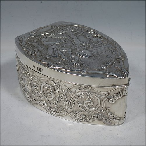 An Antique Edwardian Sterling Silver large jewellery box, having an almost heart-shaped body, with hand-chased floral and scroll decoration, a hinged lid with a hand-chased scene of a lady sitting in a boat with a gentleman presenting a rose standing on the banks of a river, and a maroon velvet-lined interior, all sitting on a flat base. Made by Samuel Jacob of London in 1902. The dimensions of this fine hand-made antique silver jewellery box are length 15 cms (6 inches), width 11 cms (4.3 inches), and height 7 cms (2.75 inches).