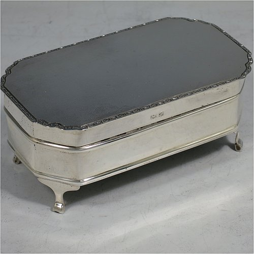 A Sterling Silver Art Deco style jewellery box, having an elongated octagonal body with plain panelled sides, a hinged lid with an applied bright-cut border and engine-turned decoration, a blue velvet-lined and gold-gilt interior, and sitting on four elegant cabriolet legs. Made by Alexander Clarke & Co., of Birmingham in 1931. The dimensions of this fine hand-made silver jewelery box are length 11.5 cms (4.5 inches), width 6.5 cms (2.5 inches), and height 5 cms (2 inches).