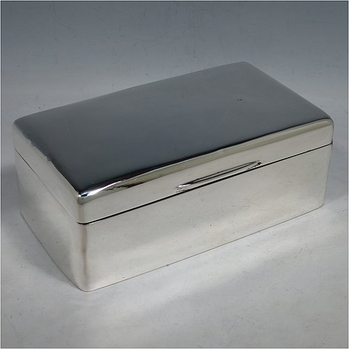 An Antique Edwardian Sterling Silver large jewelery box, having a very plain rectangular body with rounded corners, a slightly domed and hinged lid with thumb-piece and gold-gilt interior, and the base with a dark blue velvet lining. Made in London in 1905. The dimensions of this fine hand-made antique silver jewellery table box are height 7 cms (2.75 inches), length 17 cms (6.75 inches), and width 9.5 cms (3.75 inches).