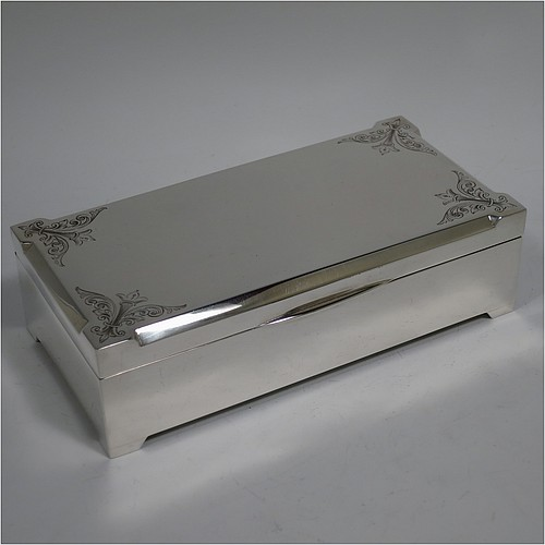 A large Art Deco Sterling Silver jewelery box, having a very plain rectangular body sitting on four corner feet, with angular hand-engraved top corners, a slightly concave and hinged lid with thumb-piece and gold-gilt interior, and the base with a light blue velvet lining. Made by Percy James Finch of Birmingham in 1930. The dimensions of this fine hand-made silver jewellery table box are height 5 cms (2 inches), length 18 cms (7 inches), and width 9 cms (3.7 inches).