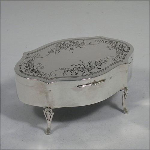 A very pretty Antique Sterling Silver jewelery box, having an oval-shaped body with straight sides, a flat hinged lid with hand-engraved floral decoration, a gold gilt and dark green velvet-lined interior, and all sitting on four cast foliate feet. Made by Henry Matthews of Birmingahm in 1912. The dimensions of this fine hand-made antique silver jewellery box are length 10cms (4 inches), width 7cms (2.75 inches), and height 5 cms (2 inches)