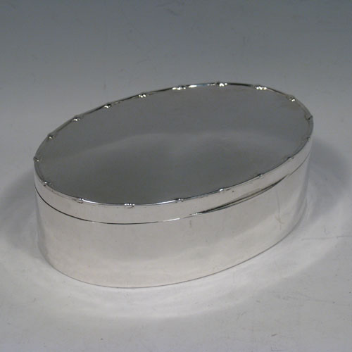 Antique Edwardian sterling silver jewelery box, having a plain oval straight-sided body, with a hinged lid and pearl border, together with a maroon velvet-lined interior. Made by William Comyns of London in 1905. Length 17 cms (6.75 inches), width 12 cms (4.75 inches), height 5.5 cms (2.25 inches). Weight approx. 345g (11 troy ounces).