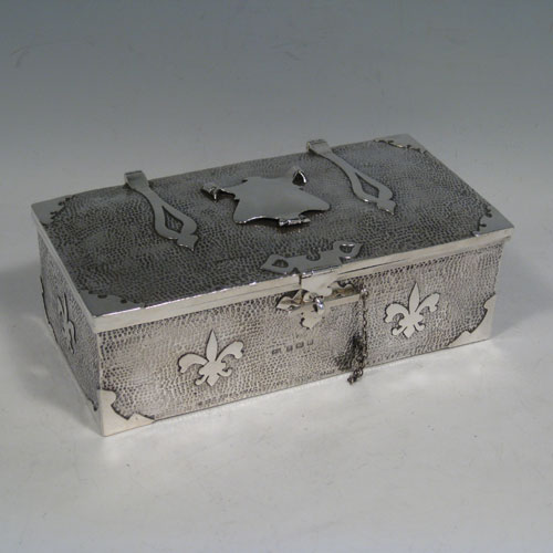 Antique Edwardian sterling silver Arts and Crafts style casket jewelery box, having a hand-hammered rectangular body, with cut-card work in a Medieval style, a hinged lock and chain, and a velvet lined interior. Made by J. Gilbert of Birmingham in 1906. Height 6.5 cms (2.5 inches), length 18.5 cms (7.25 inches), depth 10 cms (4 inches). Weight approx. 400g (13 troy ounces).