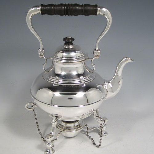 Sterling silver tea kettle on a burner stand, having a plain round baluster body with reeded decoration, a lift-off lid with wooden finial, a hinged handle with wooden insert, and sitting on an original burner stand with retaining pins and three cast hoof feet. Made by Robert Comyns of London in 1929. The dimensions of this fine silver kettle are length 21 cms (8.25 inches), height 28 cms (11 inches), width 14.5 cms (5.75 inches), and the total weight is approx. 1,000g (32 troy ounces).