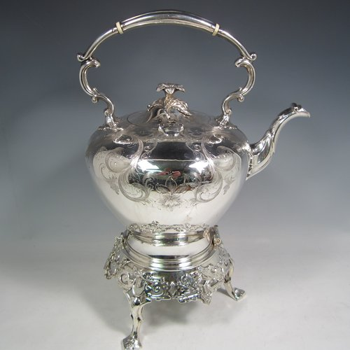 Antique Victorian silver-plated tea kettle on a burner stand, having a round baluster body with hand-engraved floral decoration, a hinged lid with flower finial, an insulated handle, and all sitting on an original burner stand with retaining pins and three cast feet. Made in ca. 1870. The dimensions of this fine silver-plated  kettle are length 28 cms (11 inches), height 41 cms (16 inches), and width 20 cms (8 inches).