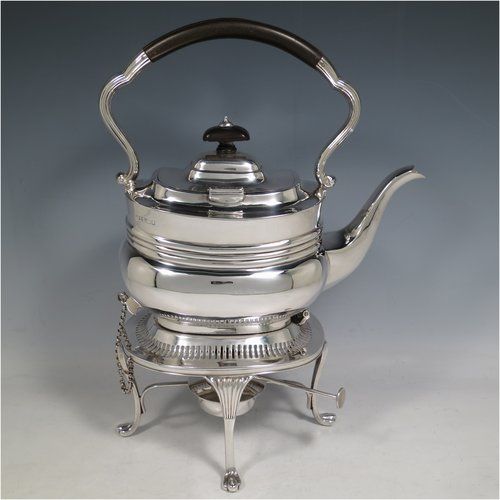An Antique Edwardian Sterling Silver tea kettle on a burner stand, having a Georgian style rectangular baluster body, with a hinged domed lid, an insulated wooden handle and finial, and sitting on an original burner stand with a pierced border and four fluted feet. Made by Mappin & Webb of Sheffield in 1903. The dimensions of this fine hand-made antique silver kettle are length 23 cms (9 inches), height 33 cms (13 inches), width 15 cms (6 inches), and the total weight is approx. 1,145g (37 troy ounces).