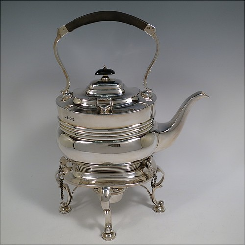 An Antique Edwardian Sterling Silver tea kettle on a burner stand, having a Georgian style rectangular baluster body, with a hinged domed lid, an insulated wooden handle and finial, and sitting on an original burner stand and four cast foliate feet. Made by Fordham and Faulkner of Sheffield in 1905. The dimensions of this fine hand-made antique silver kettle are length 23.5 cms (9.5 inches), height 33 cms (13 inches), width 15 cms (6 inches), and the total weight is approx. 1,350g (43.5 troy ounces).