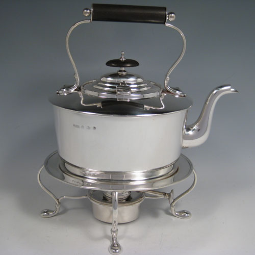 Sterling silver tea kettle on a burner stand, having a very plain oval straight-sided body, with hinged lid, insulated wooden handle and finial, and sitting on an original burner stand with four scroll feet. Made by Daniel and Arter of Birmingham in 1917. The dimensions of this fine silver kettle are length 23 cms (9 inches), height 26 cms (10.25 inches), width 15 cms (6 inches), and the total weight is approx. 1,085g (35 troy ounces).