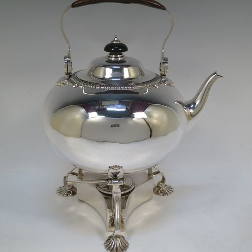 A very handsome Antique Victorian Sterling Silver tea kettle on a burner stand, having a plain round bellied body with an applied gadroon border, a lift-off lid with wooden finial, a leather covered hinged handle, and sitting on an original burner stand with removable central wick and three cast shell feet. Made by Joshua Vander of London in 1893. The dimensions of this fine hand-made antique silver kettle are length 21 cms (8.25 inches), height 27.5 cms (10.75 inches), width 18 cms (7 inches), and the total weight is approx. 770g (24.8 troy ounces).