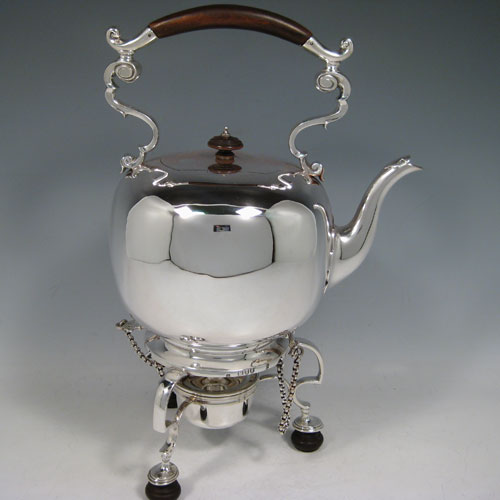 Antique Victorian sterling silver kettle on a burner stand in an early George I style, having a very plain round body, with wooden insulated scroll handle, a plain spout, a hinged lid with invisible hinge and wooden finial, and all sitting on a frame with original burner and securing pins with chains. All made by Thomas and Walter Slater of London in 1895. The dimensions of this fine hand-made silver kettle are height 32 cms (12.5 inches), length 21 cms (8.25 inches), and it weighs approx. 1,178g (38 troy ounces).