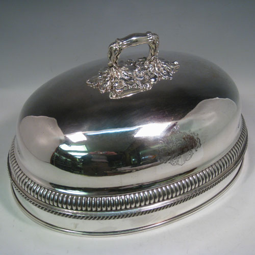 Antique Georgian Old Sheffield plated meat cover dome, having an oval plain body, with a gadroon band and reeded borders, cast acanthus leaf handle, and armorial crest. Made in ca. 1815. With original tin-backed interior. Length 41 cms (16 inches), width 30 cms (12 inches).