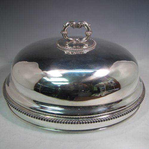 Antique Georgian Old Sheffield plated meat cover dome, having an oval plain body, with gadroon borders, a cast asparagus scroll handle, and with original tin-backed interior. Made in ca. 1815. The dimensions of this fine hand-made Old Sheffield plated meat cover dome are length 51 cms (20 inches), width 39 cms (15.5 inches), and height (inc. handle) 30 cms (12 inches). Please note that this item is crested.