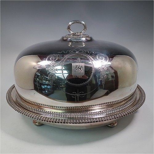 An Antique Georgian Old Sheffield plated meat cover dome and warming stand platter, having a plain oval body with Regency style gadroon and fluted border, a cast reeded loop handle, and all sitting on a well and tree dish for carving, having a hot water jacket, and with matching decoration, and sitting on four cushion feet. Made in the Regency period ca. 1815. The dimensions of this fine hand-made Old Sheffield plated meat cover dome and hot water stand are length (inc. handles) 53 cm (21 inches), width 42 cms (16.5 inches), and height 34 cms (13.5 inches). Please note that the meat dome is engraved and crested on one side.
