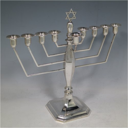 A Sterling Silver Hanukkah Menorah in an Art Deco style, having an octagonal panelled body sitting on a pedestal foot, with a removable Shamus candle holder. Made in Birmingham in 1948. The dimensions of this fine hand-made silver menorah are height 23 cms (9 inches), spread across arms 25 cms (9.75 inches), and it weighs approx. 248g (8 troy ounces) Please note that this item is not filled so the whole weight is silver.