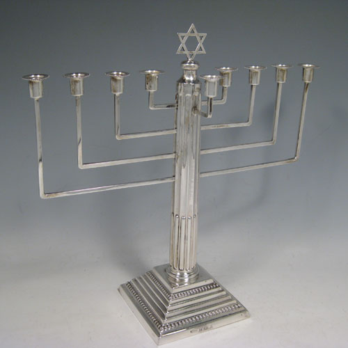 Sterling silver Menorah, having a stepped base with bead borders, and a fluted corinthian style column. Made in Birmingham in 1930. Height 28 cms (11 inches), spread across arms 28 cms (11 inches). Weight approx. 420g (13.5 troy ounces) Please note that this item is not filled.