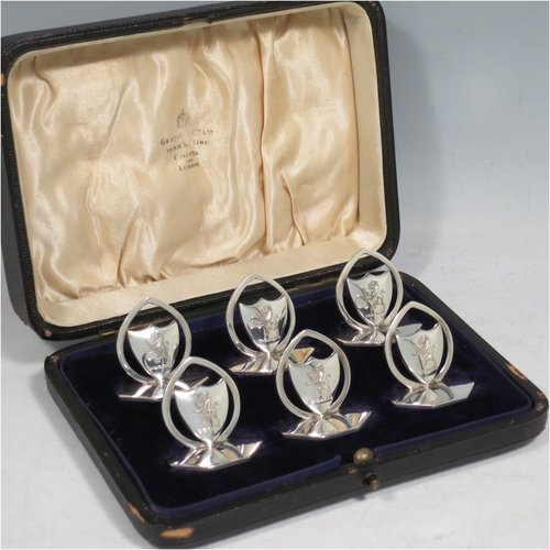 An Antique Sterling Silver set of six place card holders, having shield-shaped bodies, each mounted in a pointed ring on an octagonal base, and all in their original satin and velvet-lined presentation box. Made by William Hutton of London in 1912. The dimensions of this fine set of antique silver place card holders are width of bases 3.5 cms (1.25 inches), height 3 cms (1.25 inches), and they weigh a total of approx. 140g (4.5 troy ounces). Please note that each on is engraved with a rampant lion.