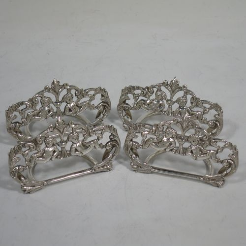 A very pretty Antique Victorian Sterling Silver set of four place card holders, having cast bodies with reclining cherubs over scroll and floral decoration, and sitting on half-circle wire-work bases. Made by Samuel Jacob of London in 1894. The dimensions of this fine set of antique silver place card holders are width 7 cms (2.75 inches), height 4 cms (1.5 inches), depth 3 cms (1.25 inches), and they weigh a total of approx. 106g (3.4 troy ounces).