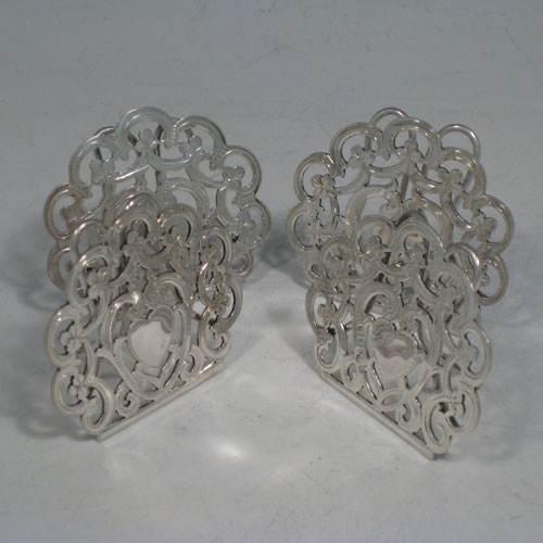 Antique Victorian sterling silver set of four menu or place card holders, having hand-pierced work with scrolls, three-leaf clovers, and heart-shaped cartouches. Please note that two are made in Birmingham in 1899, and two are marked sterling made in ca. 1890. Height 5 cms (2 inches), width 5 cms (2 inches). Total weight approx. 78g (2.5 troy ounces).