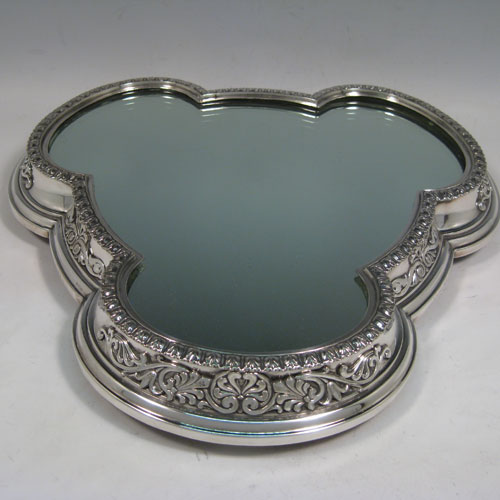 Antique Victorian silver-plated mirror plateau, having a very unusual tri-lobed shaped body, applied floral and scroll borders, and an original oak base with three hinged feet for ease of cleaning. Made by Elkington and Co., with their date letter for 1873. The dimensions of this fine hand-made mirror plateau are width 34 cms (13.5 inches), and height 5 cms (2 inches).