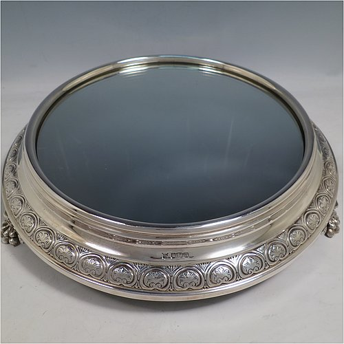 An Antique Edwardian Sterling Silver mirror plateau, having a round body with hand-chased floral decoration, a plain reeded border surrounding the mirror, all sitting on three cast foliate and lions-paw feet, and an original oak base underneath. Made by the Deakin Brothers of Sheffield in 1904. The dimensions of this fine hand-made antique silver mirror plateau are diameter 38 cms (15 inches), and height 9 cms (3.5 inches).