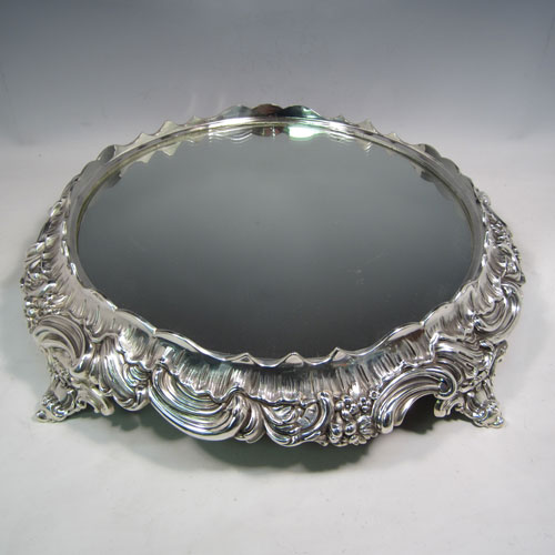 Antique Victorian silver-plated mirror plateau, having a round body, with hand-chased floral decoration, and sitting on four foliate feet. Made in ca. 1880. The dimensions of this fine hand-made silver-plated mirror plateau are diameter 43 cms (17 inches), and height 9 cms (3.5 inches).