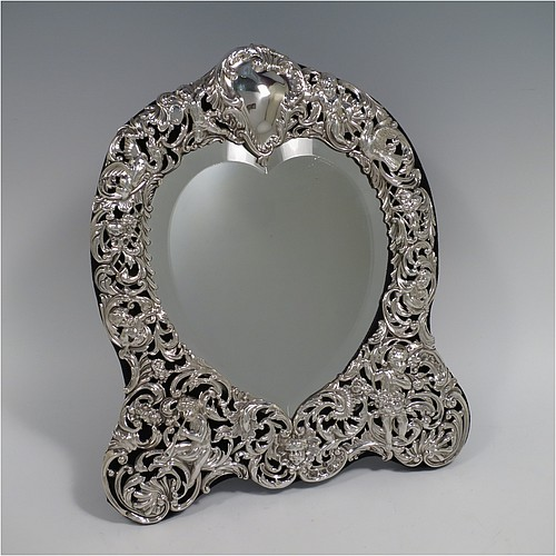 An Antique Victorian Sterling Silver table or vanity mirror having hand-chased cherubs and birds, scroll-work, and floral decoration, with a top vacant cartouche, an original bevelled heart-shaped mirror, and blue velvet backing with easel stand. Made by William Comyns of London in 1893. The dimensions across the frame of this fine hand-made antique silver vanity or table mirror are height 28 cms (11 inches), and width 24 cms (9.5 inches).