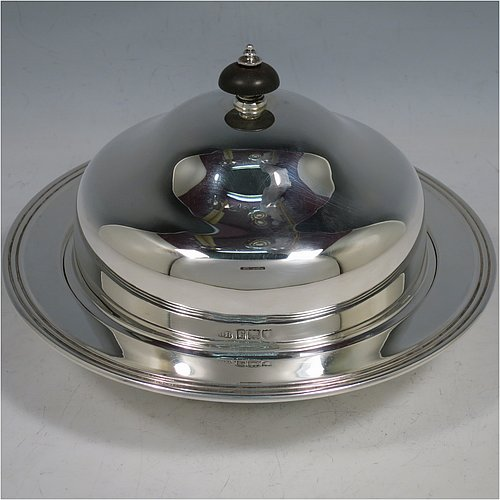 An Antique Sterling Silver muffin dish, having a plain round body with reeded border, a domed lift-off lid with wooden finial, an interior lift-out liner with space underneath for hot water or crushed ice, and sitting on a flat base. Made by Harrison Brothers & Howson of in 1912. The dimensions of this fine hand-made antique silver muffin dish are diameter 18.5 cms (7.3 inches), height 11.5 cms (4.5 inches), and it weighs approx. 486g (15.7 troy ounces).