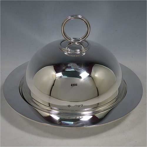 An Antique Victorian Sterling Silver covered muffin dish, having a plain domed lift-off lid with a round reeded handle, sitting on a plain round deep dish with a flat base. Made by William Hutton and Sons of London in 1895. The dimensions of this fine hand-made antique silver muffin dish are height 15 cms (6 inches), diameter of base dish 23 cms (9 inches), and with a total weight of approx. 788g (25 troy ounces).