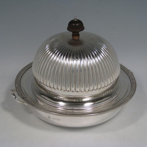 Antique Victorian sterling silver covered muffin dish, having a lift-off lid with half-fluted decoration and wooden finial, a removable plate (which can double as a serving dish) with a gadroon edge, and a deep base for hot water (or crushed ice) with two cast handles. Made by William Hutton and Sons of London in 1898. Height 15 cms (6 inches), diameter of removable plate 20 cms (8 inches). Total weight approx. 550g (17.7 troy ounces).