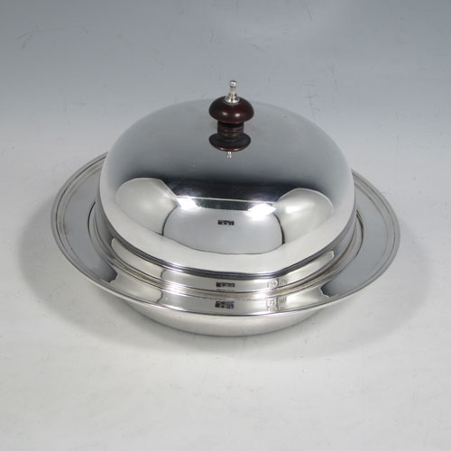 Sterling silver muffin dish, having a plain round body, with lift-off lid and wooden finial, an interior lift-out liner, and sitting on a flat base. Made by the Adie Brothers of Birmingham in 1939. The dimensions of this fine hand-made silver muffin dish are diameter 18 cms (7 inches), height 10 cms (4 inches), and it weighs approx. 480g (15.5 troy ounces).