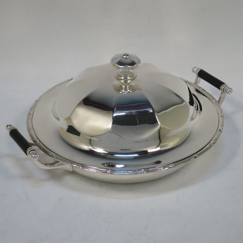 A handsome Antique Sterling Silver muffin dish, having a round body with an applied ribbon and reed border, with two side handles having black ebonised inserts, a domed and panelled lift-off lid with cast finial, and all sitting on a flat base. Made by James Dixon and Sons of Sheffield in 1911. The dimensions of this fine hand-made antique silver muffin dish are diameter 18 cms (7 inches), height 9 cms (3.5 inches), and it weighs approx. 330g (10.6 troy ounces).