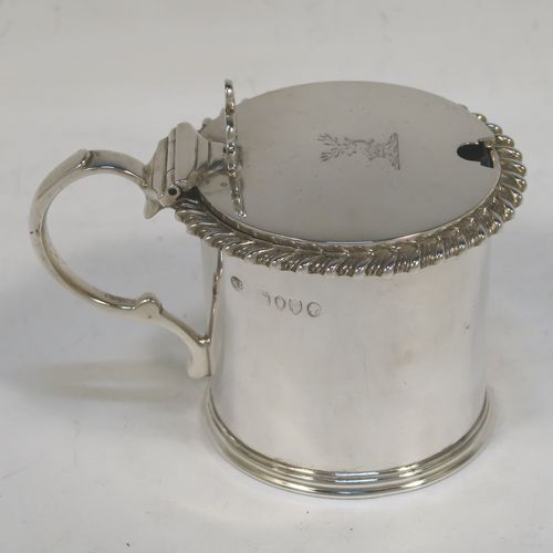 Antique Victorian sterling silver drum mustard, having a plain cylindrical body with a gadroon border, a hinged flat lid with hand-pierced thumb-piece, a scroll handle and a blue glass liner. Madee by William Evans of London in 1881. The dimensions of this fine hand-made silver mustard pot are height 7 cms (2.75 inches), diameter 6.5 cms (2.5 inches), and it weighs approx. 114g (3.7 troy ounces). Please note that this item is crested on the lid.