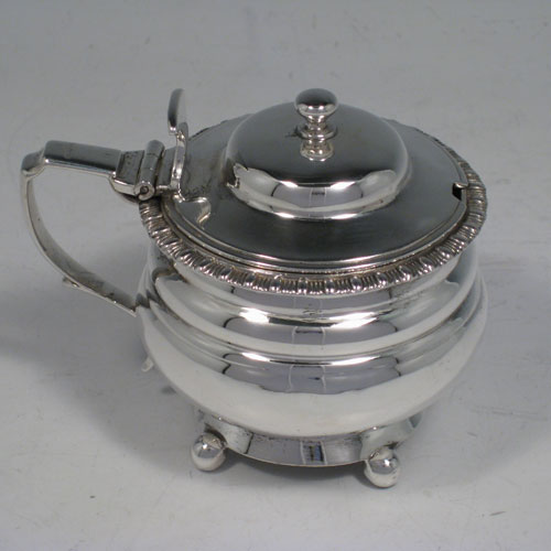 Antique Georgian sterling silver round mustard pot sitting on four ball feet, having a hinged lid and ball finial, gadroon edge, and blue-glass liner. Made by Thomas Johnson of London in 1825. Length 10 cms (4 inches), diameter 7 cms (2.75 inches), height 8 cms (3.25 inches). Weight approx. 5 troy ounces (155g).