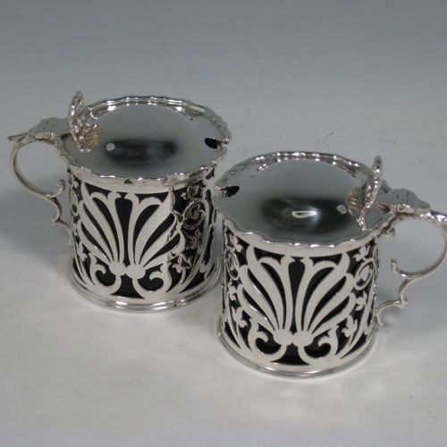 Antique Edwardian sterling silver pair of mustard pots, having Art Nouveau hand-pierced round bodies, with cast scroll handles, hinged lids with shell thumb-pieces, and blue glass liners. Made by Charles Clement Pilling of Sheffield in 1901/1902. Height 7 cms (2.75 inches), diameter 6 cms (2.3 inches). Total weight approx. 202g (6.5 troy ounces).
