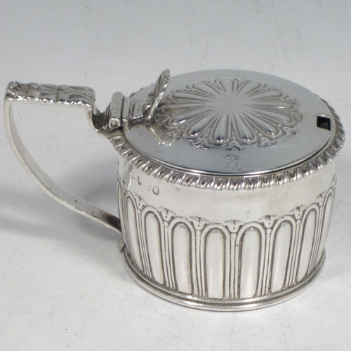 Antique Georgian Regency sterling silver mustard pot, having a round body with hand-chased fluted straight sides, a gadroon-edged border, a hinged lid with shell thumb-piece, a blue glass liner and scroll handle, all sitting on a flat base. Made by Rebecca Emes and Edward Barnard of London in 1817. The dimensions of this fine hand-made silver mustard pot are height 6.5 cms (2.5 inches), diameter 7 cms (2.75 inches), and it weighs approx. 146g (4.7 troy ounces).