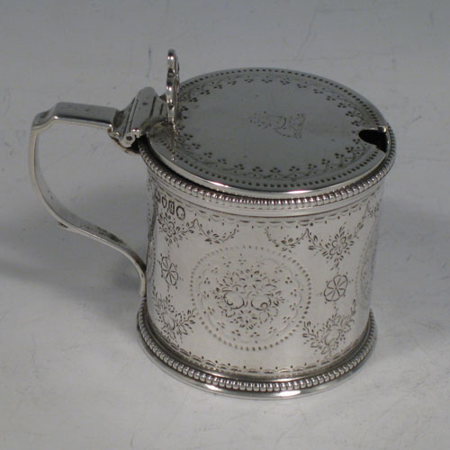 Antique Victorian sterling silver mustard pot, having a round straight-sided body with hand-engraved floral decoration, bead-edged borders, a hinged lid with pierced thumb-piece, a blue glass liner and scroll handle. Made by William Eaton of London in 1871. The dimensions of this fine hand-made silver mustard pot are height 7 cms (2.75 inches), diameter 6 cms (2.3 inches), and it weighs approx. 108g (3.5 troy ounces).