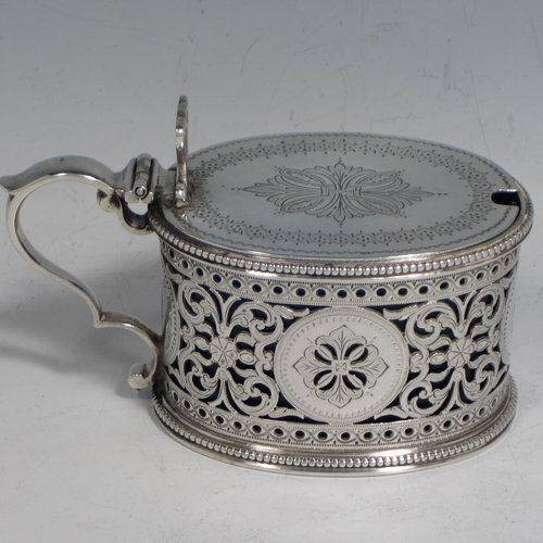 Antique Victorian sterling silver mustard pot, having an oval straight-sided body with beautiful hand-pierced and engraved floral decoration, with applied bead borders, a hinged flat lid with hand-pierced thumb-piece, a scroll handle and a blue glass liner. Made by the Barnard Brothers of London in 1875. The dimensions of this fine hand-made silver mustard pot are height 7 cms (2.75 inches), length 11 cms (4.25 inches), and it weighs approx. 140g (4.5 troy ounces). Please note that this item is crested and monogrammed.