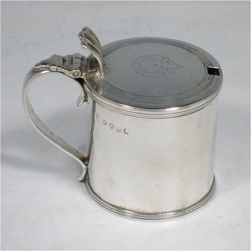 An Antique Georgian Sterling Silver drum mustard pot, having a plain cylindrical body, with applied reeded borders, a hinged lid with pierced thumb-piece, a plain scroll handle, and an internal blue glass liner. Made by Rebecca Emes & Edward Barnard I of London in 1818. The dimensions of this fine hand-made antique silver mustard pot are height 8 cms (3 inches), diameter 6 cms (2.3 inches), and it weighs approx. 144g (4.6 troy ounces). Please note that this item has an engraved crest on the top of the lid.