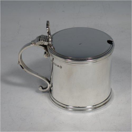 A Sterling Silver drum mustard pot, having a plain cylindrical body, a flat hinged lid with pierced thumb-piece, with applied reeded borders, a scroll handle, and blue-glass liner. Made by Robert Comyns of London in 1935. The dimensions of this fine hand-made silver mustard pot are height 7 cms (2.75 inches), diameter 8 cms (2.3 inches), and it weighs approx. 125g (4 troy ounces).