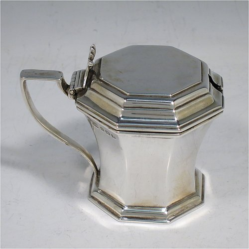 A Sterling Silver mustard pot, having a plain hexagonal panelled body with tapering sides, a hinged stepped flat-topped lid with hand-pierced thumb-piece, a plain scroll handle, an original blue-glass liner, and sitting on a flat base. Made by Carrington & Sons of Birmingham in 1924. The dimensions of this fine hand-made silver mustard pot are length 9.5 cms (3.75 inches), height 8 cms (3 inches), and it weighs approx. 129g (4.1 troy ounces).