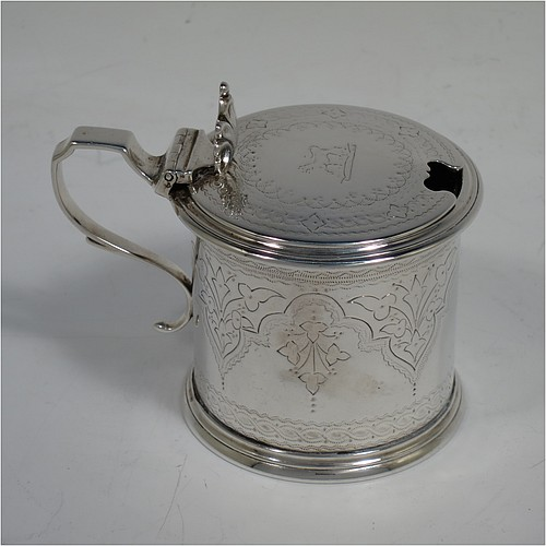 A very pretty Antique Victorian Sterling Silver drum mustard, having a cylindrical body with hand-engraved floral and scroll decoration, with applied reeded borders, a hinged flat lid with a cast floral thumb-piece, a scroll handle and a blue glass liner. Made by Edward Barnard of London in 1875. The dimensions of this fine hand-made antique silver mustard pot are height 8 cms (3 inches), diameter 6.5 cms (2.5 inches), and it weighs approx. 125g (4 troy ounces). Please note that this item is crested on the lid.