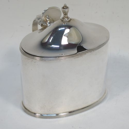 A very handsome and large Scottish Sterling Silver mustard pot, having a plain oval body with slightly curved sides, with applied reeded borders, a domed lid with an urn-shaped finial, a scroll side-handle with plain oval thumb-piece, and a fitted blue glass liner. Made by Robert Sawers Ltd of Edinburgh in 1936. The dimensions of this fine hand-made Scottish silver mustard pot are height 8.5 cms (3.3 inches), length 8 cms (3 inches), depth  (inc. handle) 8 cms (3 inches), and it weighs approx. 108g (3.5 troy ounces).