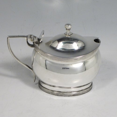 Antique Georgian sterling silver mustard pot, having a plain oval baluster body, a hinged domed lid with thumb-piece and ball finial, with applied reeded borders, a reeded scroll handle, a blue glass liner, all sitting on a flat base. Made by John Gold of London in 1801. The dimensions of this fine hand-made silver mustard pot are height 8 cms (3 inches), length 11 cms (4.25 inches), width 6 cms (2.25 inches), and it weighs approx. 115g (3.7 troy ounces).