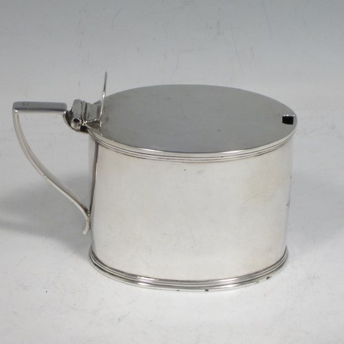 Antique Georgian sterling silver drum mustard pot, having a plain oval body with applied reeded borders, a flat hinged lid with thumb-piece, a scroll handle, and a blue-glass liner. Made by John Emes of London in 1804. The dimensions of this fine hand-made silver mustard pot are length 10 cms (4 inches), height 7.5 cms (3 inches), width 5 cms (2 inches), and it weighs approx. 137g (4.4 troy ounces). Please note that this item is crested.