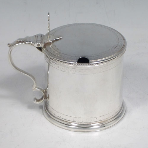 Antique Georgian sterling silver drum mustard pot, having a round body with straight sides, with subtle hand-engraved bands of floral decoration, a bead-edged top border, a hinged lid with pierced thumb-piece, a blue glass liner and scroll handle, all sitting on a flat base. Made by Robert Hennell of London in 1784. The dimensions of this fine hand-made silver mustard pot are height 8 cms (3 inches), diameter 6 cms (2.3 inches), and it weighs approx. 110g (3.5 troy ounces).