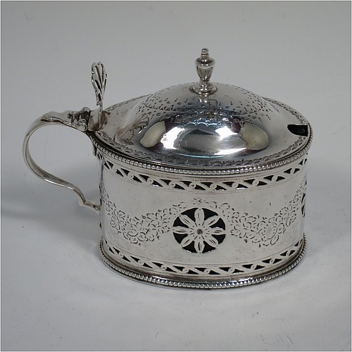 An Antique Georgian Neoclassical Sterling Silver mustard pot, having an oval body with straight sides, with hand-pierced and engraved neoclassical style floral decoration, a hinged and domed lid with urn shaped finial and pierced thumb-pierce, a scroll handle, a blue glass liner, and all sitting on a flat base. Made by Robert Hennell I  of London in 1773. The dimensions of this fine hand-made antique silver mustard pot are height 8 cms (3.25 inches), length 10 cms (4 inches), width 5.5 cms (2.25 inches), and it weighs approx. 93g (3 troy ounces).